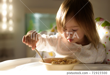 Small girl eats brakefast by herself with a spoon. 72915500