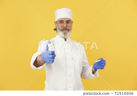 Old doctor standing in a white uniform 72918806