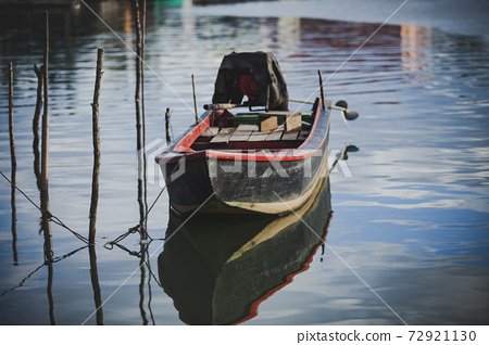 old wooden boat floating over plain water 72921130