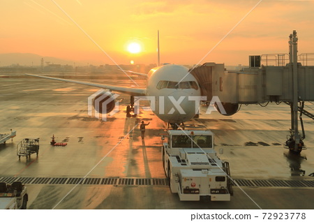 An airplane that is about to leave with the setting sun in the background 72923778