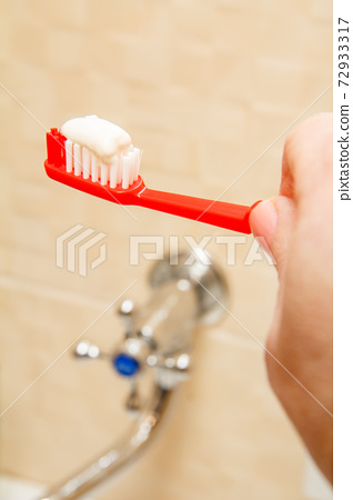 Red toothbrush with white toothpaste in female hands. 72933317