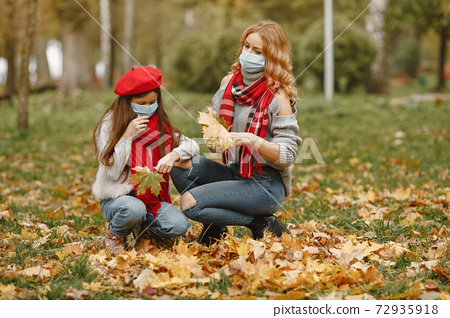 Mother with daughter walks outside in masks 72935918