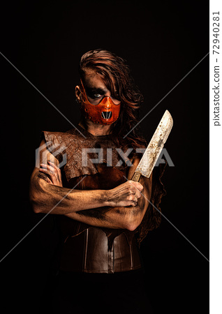 Portrait of a murderous savage wearing a leather mask, armed with a knife she is holding in her hand 72940281
