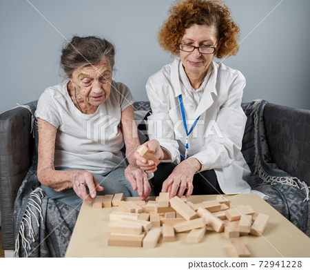 Senior woman playing Jenga, build tower of blocks. Elderly doctor in white lab coat, supporting senior patient, developing logic, fine motor skills, Alzheimer disease at home with old lonely female 72941228