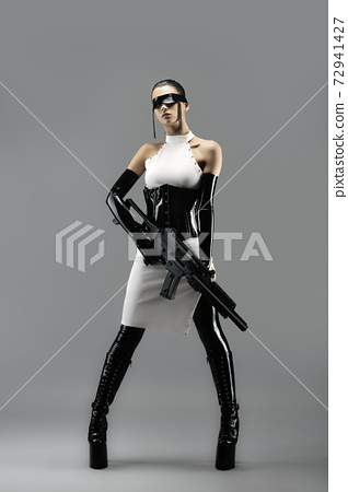 Futuristic portrait of a pretty young woman in a white dress, wearing a waist cincher, gloves, a black latex headband and an assault rifle in her hands 72941427