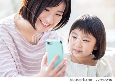 家人和媽媽看著智能手機 72947240