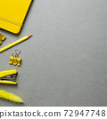 Yellow stationery office supplies. Notebook, clip, pencil, stapler on gray background. flat lay, top view, copy space 72947748