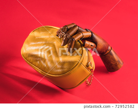 Wooden hand holding yellow leather bag on red 72952582