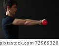 Personal trainer demonstrating dumbbell workout 72969320