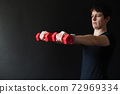 Personal trainer demonstrating dumbbell workout 72969334
