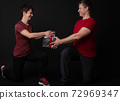 Personal Trainer couple handing a gift box 72969347