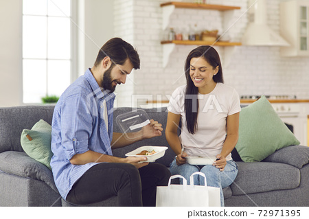 Smiling couple man and woman unpacking healthy boxed food order delivered to home by courier 72971395