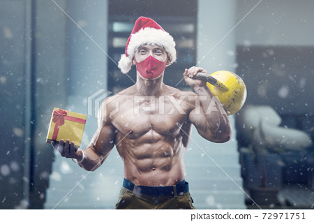 Fitness man in Santa Claus hat costume in gym 72971751