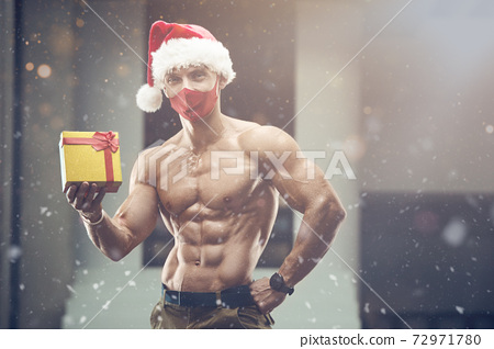 Fitness man in Santa Claus hat costume in gym 72971780