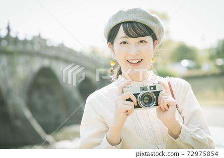帶著照相機在旅遊區中的女人 72975854