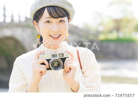 帶著照相機在旅遊區中的女人 72975857