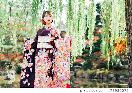 A woman in a kimono (furisode) standing under a willow tree 72980072