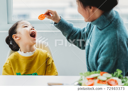Mother and daughter eating 72983373