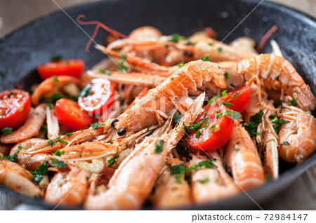 Scampi cooked with tomatoes and parsley in a pan 72984147