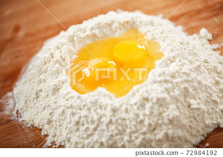 Flour and eggs as ingredients for making pasta dough. 72984192