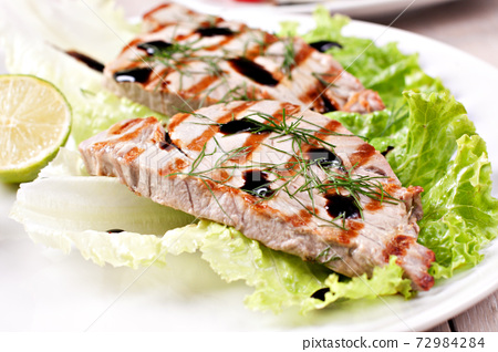 Grilled tuna with salad on a plate ready to eat. 72984284
