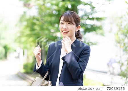 녹색을 배경으로 서 정장 미소의 젊은 여성 72989126