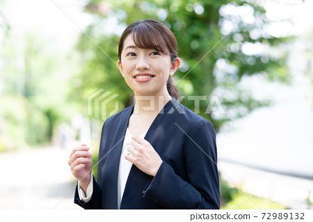 녹색을 배경으로 서 정장 미소의 젊은 여성 72989132