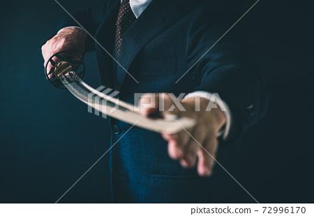 一個穿著西裝拿著日本劍的人 72996170