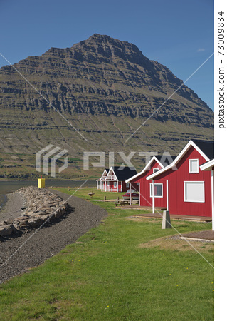 Traditional red painted wooden panel house with mighty Holmatindur mountain in the background in Eskifjordur, East Iceland 73009834