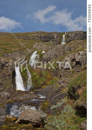 Beautiful cascade waterfall Bleiksarfoss in Eskifjordur, east of Iceland 73009948