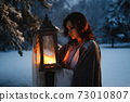 Beautiful fairytale shot of young woman looking at vintage lantern emitting warm light. Medieval fantasy concept 73010807