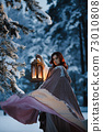 Epic fantasy shot: Young woman spinning her flying cloak holding vintage lantern in snowy forest at night. Medieval fairytale cosplay concept 73010808