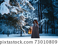Fantasy cosplay: Young woman with vintage lantern looking at fir tree covered in snow. Medieval fairytale concept 73010809