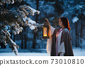Fantasy: Young woman holds vintage lantern lighting fir tree covered in snow in the evening. Medieval fairytale cosplay concept 73010810