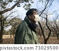一個六十多歲的男子戴著面具,在寒冷的日子在公園散步 73029500