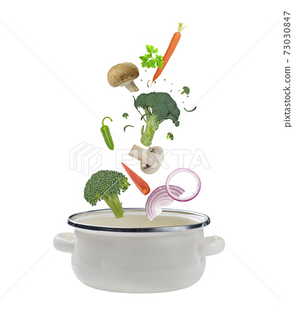 Fresh vegetables falling into a  cooking casserole pot. Isolated on white 73030847