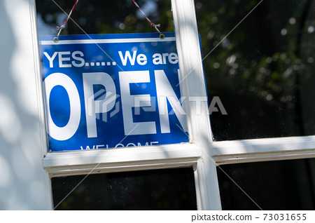 Blue open sign hanging on the white entrance door of a business office 73031655