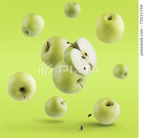 ripe whole and cut apple with seeds and leaves isolated on green background. 73031749