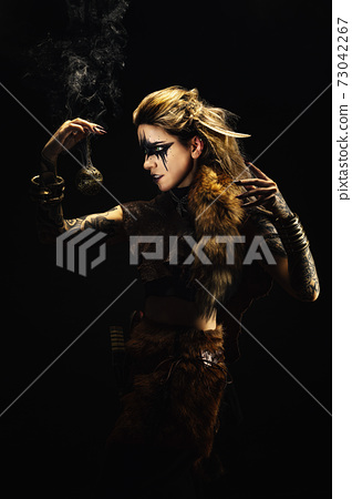 Portrait of a young viking shaman holding a ball of incense in his hands 73042267