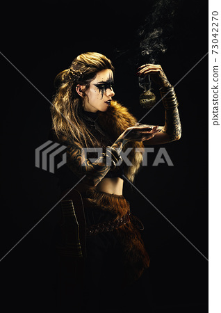 Portrait of a young viking shaman holding a ball of incense in his hands 73042270