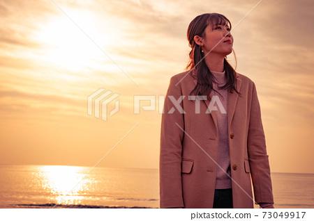 在日落時享受大海的年輕女子 73049917