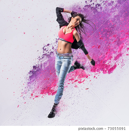 Fit dancer jumping into the paint splash 73055091