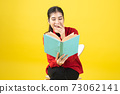 Asian women are reading a book or novel, enjoying and happy, the woman is opening a book in the hand and accidentally read it on yellow background with copy space. 73062141