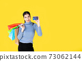 Portrait of Asian happy women holding colorful shopping bags and show credit cards,looking at camera isolated on yellow background with copy sapce,shopping and lifestyle concept. 73062144