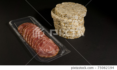 Grain crispbreads crispy rice and diet bread with smoked sausage. Rice cake puffed rice with salami, sausage, balyk, smoked meat on black background 73062194
