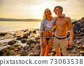 Happy couple having fun and drinking beer at the beach 73063538