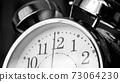 Black white big metallic clock close up. Time or showing time concept. Classic retro mechanical alarm clock 73064230