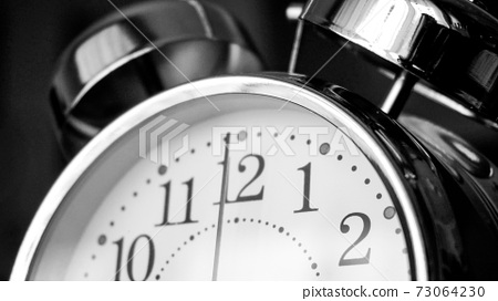 Black white big metallic clock close up. Time or showing time concept. Classic retro mechanical alarm clock 73064230