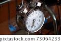 Big metallic clock close up. Time or showing time concept. Classic retro mechanical alarm clock 73064233