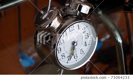 Big metallic clock close up. Time or showing time concept. Classic retro mechanical alarm clock 73064233